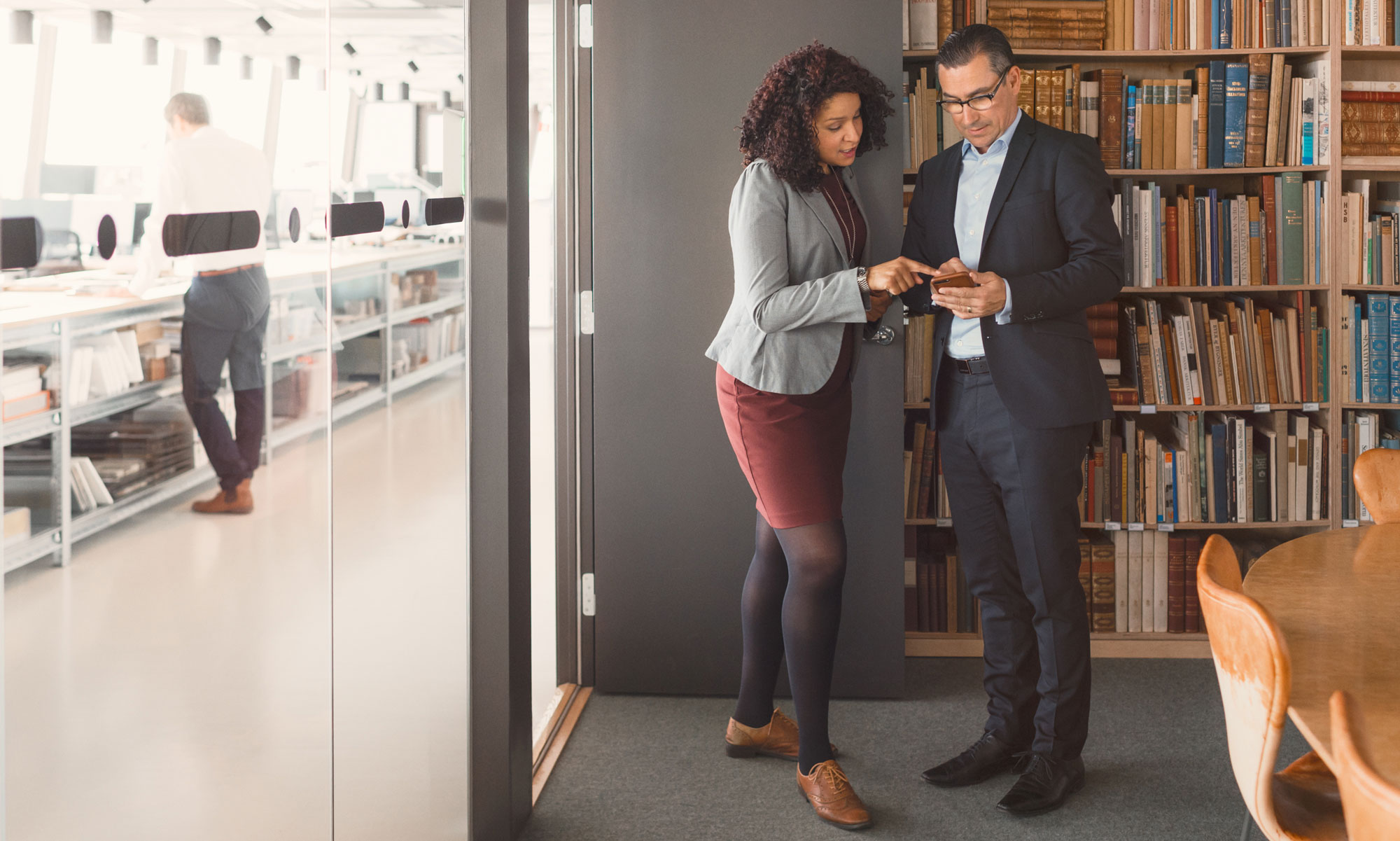 Two business people looking at a mobile in office library.